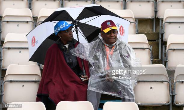 Fans look on in the rain during the Group Stage match of the ICC Cricket World Cup 2019 between South Africa and West Indies at The Hampshire Bowl on...