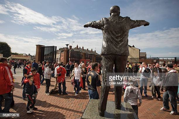 Fans looking at the statue of former Liverpool manager Bill Shankly outside Anfield home of Liverpool football club pictured before the club took on...