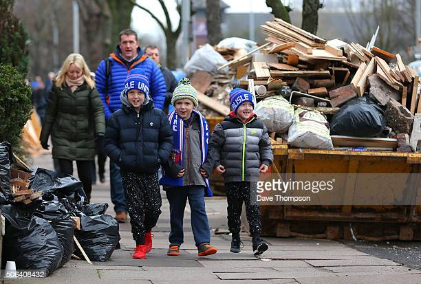 Fans make their way to the ground past debris from houses damaged by the recent floods prior to the Sky Bet League Two match between Carlisle United...
