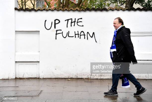 Fans make their way to the stadium past graffiti ahead of the Premier League match between Chelsea FC and Fulham FC at Stamford Bridge on December 2...