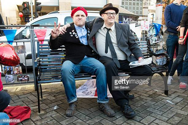 Fans Mark Adams and Lawrence Harman pose on the memorial bench for the late Rik Mayall is unveiled on November 14 2014 in London England