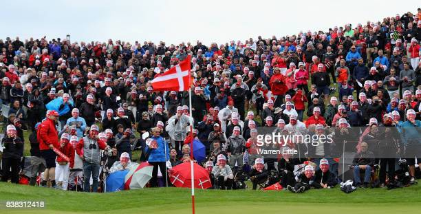 Fans mark the 500th European Tour appearance of Thomas Bjorn of Denmark by doning look a like face masks on the 16th green during the first round of...