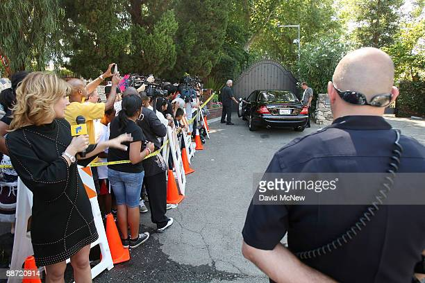 Fans members of the media and police watch as a family friend drives to the gate of the Jackson family mansion where members of the family are...