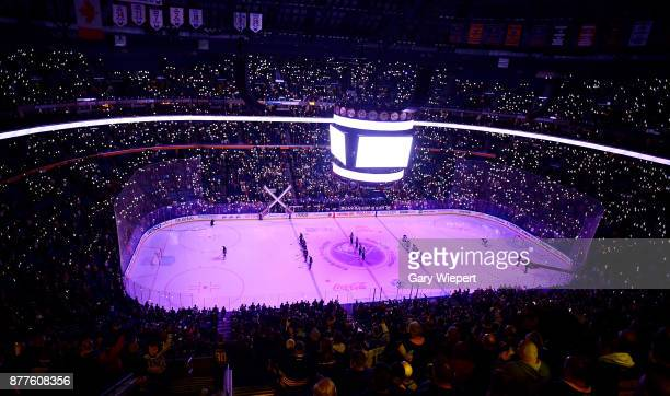 Fans observe a moment of silence and light their phones in honor of Hockey Fights Cancer prior to an NHL game between the Buffalo Sabres and...