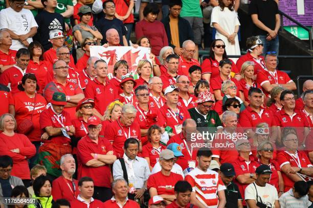 Fans observe a moment of silence for victims of typhoon Hagibis before the start of the Japan 2019 Rugby World Cup Pool D match between Wales and...