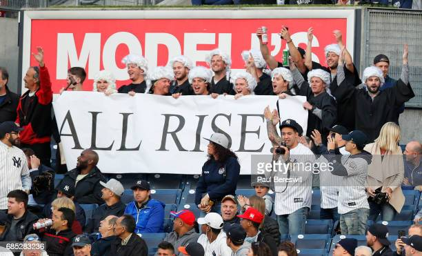 Fans of Aaron Judge of the New York Yankees stand up dressed as judges to cheer Aaron judge when he comes to bat in an MLB baseball game against the...