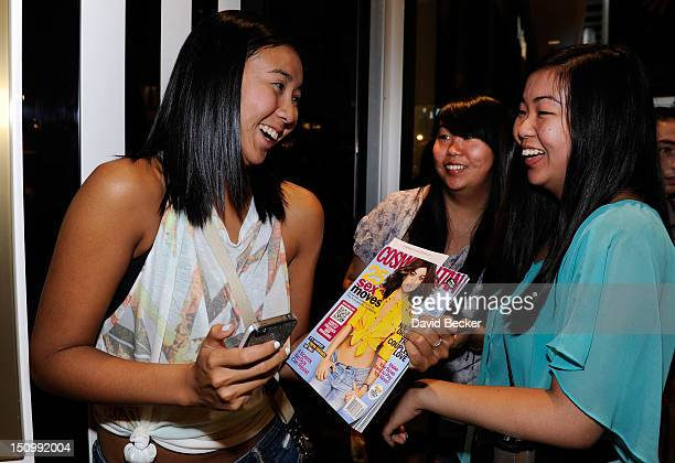 Fans of actress Lucy Hale hold a copy of a magazine with her picture during the grand opening of Henri Bendel at the Fashion Show mall on August 29...