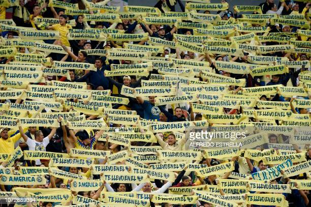 Fans of America cheer during the first round match of the final of the Mexican Apertura football tournament against Cruz Azulat the Azteca stadium in...