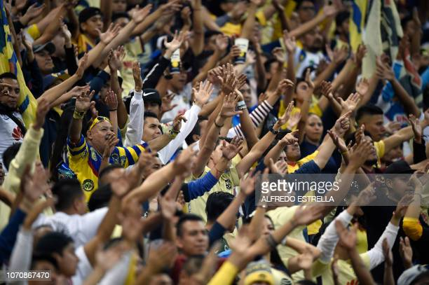 Fans of America cheer their team during the second round of semifinals of the Mexican Apertura tournament football match against Pumas at the Azteca...