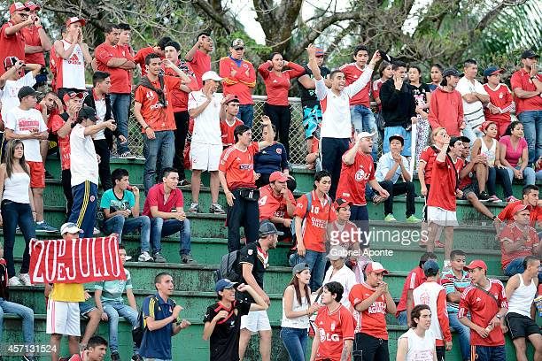 Fans of America de Cali cheer for their team during a match between America de Cali and Llaneros FC as part of Torneo Postobon 2014 II at Manuel...