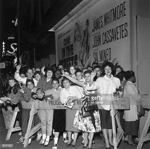 Fans of American actor Sal Mineo waving from behind a police barricade at the premiere of the Don Siegel film 'Crime in the Streets' at the Victoria...