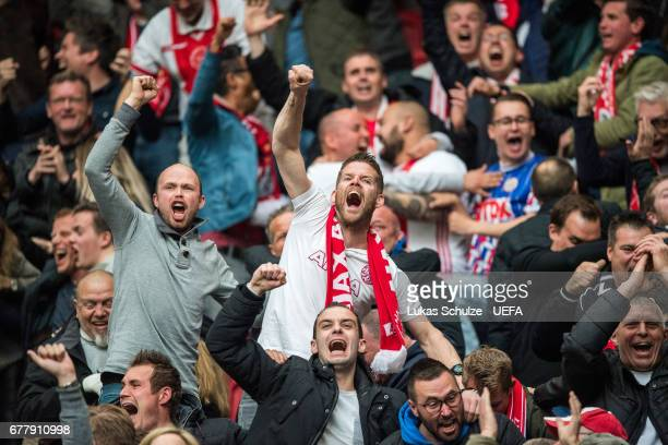 Fans of Amsterdam celebrate their teams fourth goal during the Uefa Europa League semi final first leg match between Ajax Amsterdam and Olympique...