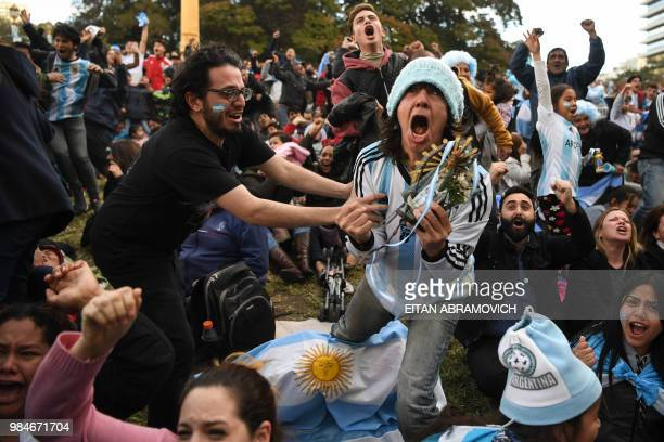 TOPSHOT Fans of Argentina watching the FIFA World Cup match against Nigeria on a large screen at San Martin square in Buenos Aires celebrate after...
