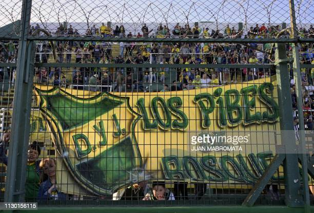 Fans of Argentina's Defensa y Justicia cheer for their team before the start of Argentina's Superliga football match against Argentinos Juniors at...