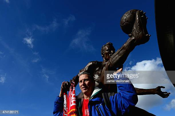 Fans of Arsenal enjoy the new former Arsenal and Netherlands footballer Dennis Bergkamp statue prior to the Barclays Premier League match between...
