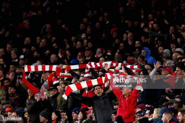 Fans of Arsenal hold up their scarves in support during the Premier League match between Arsenal FC and Manchester United at Emirates Stadium on...