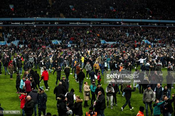 Fans of Aston Villa invade the pitch at full time during the Carabao Cup Semi Final match between Aston Villa and Leicester City at Villa Park on...