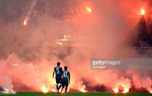 Fans of Berlin throw flares on the pitch next to Andre Mijatovic and Raffael of Berlin during the Bundesliga Relegation second leg match between...