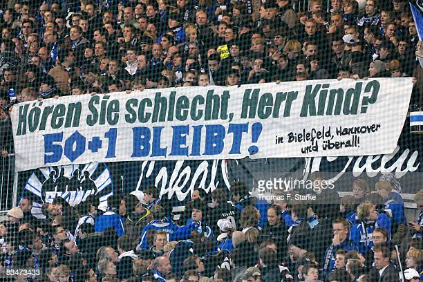 Fans of Bielefeld show a protest banner against the president of Hannover 96 Martin Kind during the Bundesliga match between Arminia Bielefeld and...