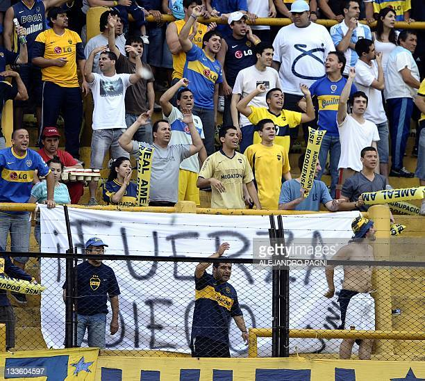 Fans of Boca Juniors cheer their team in front of a sign reading Be strong Diego in support of Argentinian former player Diego Maradona after his...