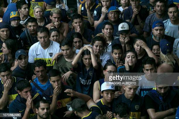 TOPSHOT Fans of Boca Juniors in Buenos Aires' La Boca neighbourhood react after their team loses the second leg match of the allArgentine Copa...