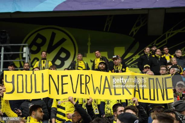 Fans of Borussia Dortmund hold up a banner saying You'll Never Walk Alone before the UEFA Champions League Quarter Final first leg match between...