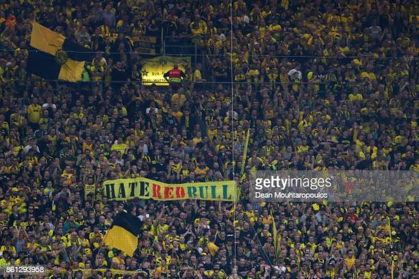 Fans of Borussia Dortmund hold up signs and flags against the club of RB Leipzig during the Bundesliga match between Borussia Dortmund and RB Leipzig...