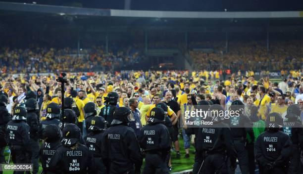 Fans of Braunschweig face police in riot gear after the Bundesliga Playoff leg 2 match between Eintracht Braunschweig and VfL Wolfsburg at Eintracht...