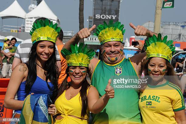Fans of Brazil cheer their team before the FIFA World Cup match against Chile at the Fan Fest in Rio de Janeiro on June 28 2014 AFP PHOTO / TASSO...