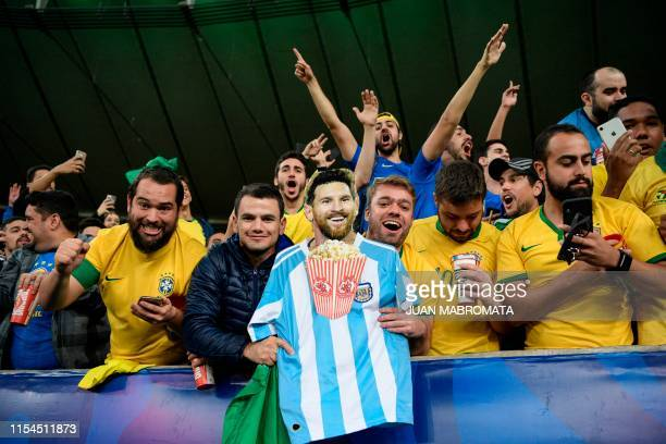 Fans of Brazil hold an image of Argentine footballer Lionel Messi eating popcorn as the celebrate after their national team won the Copa America...
