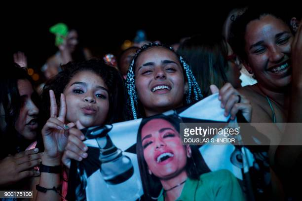 Fans of Brazilian singer Anitta cheer during the New Year's Eve Concert at Copacabana beach in Rio de Janeiro on January 1 2018 / AFP PHOTO / DOUGLAS...