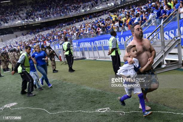 Fans of Brazil's Cruzeiro leave the tribune after clashes erupted during the Brazilian Championship football match against Palmeiras in Belo...