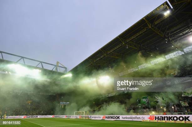 Fans of Bremen burn flares during the Bundesliga match between Borussia Dortmund and SV Werder Bremen at Signal Iduna Park on December 9 2017 in...