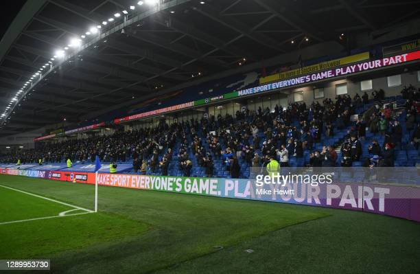 Fans of Brighton & Hove Albion applaud as a Stonewall Rainbow Laces board is seen ahead of the Premier League match between Brighton & Hove Albion...