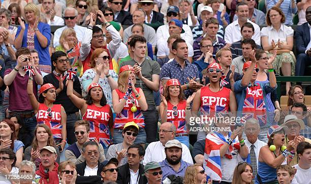 Fans of Britain's Andy Murray cheer in the crowd on Centre Court as Murray plays against Spain's Fernando Verdasco leaps during their men's singles...