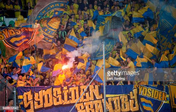 Fans of Brondby IF cheer with pyrotechnics during the Danish Alka Superliga match between FC Midtjylland and Brondby IF at MCH Arena on April 19 2018...