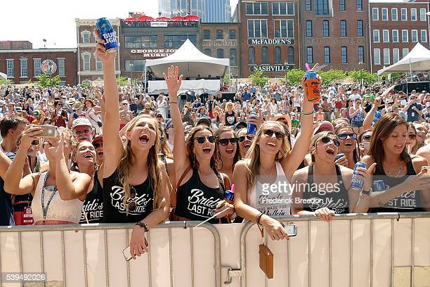 Fans of Canaan Smith cheer during a performance during the CMA Fest on the Chevrolet River Stage on June 11 2016 in Nashville Tennessee