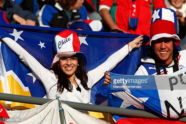 Fans of Chile and Venezuela cheer to their teams before the game between Venezuela and Chile during a quarter final match at Bicentenarium Stadium on...