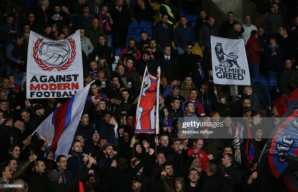 Fans of Crystal Palace hold up banners saying - Against Modern Football and Premier Greed