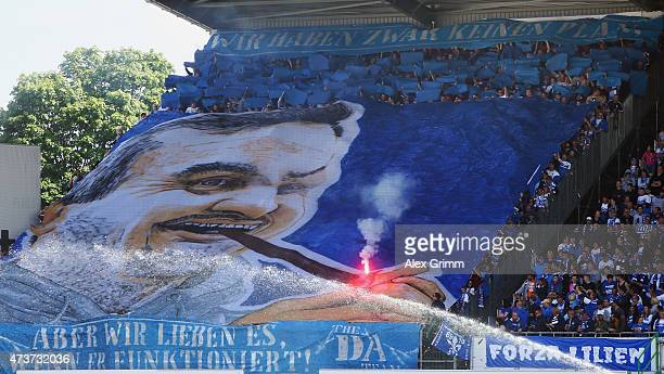 Fans of Darmstadt hold a banner with the face of their team's head coach Dirk Schuster prior to the Second Bundesliga match between SpVgg Greuther...