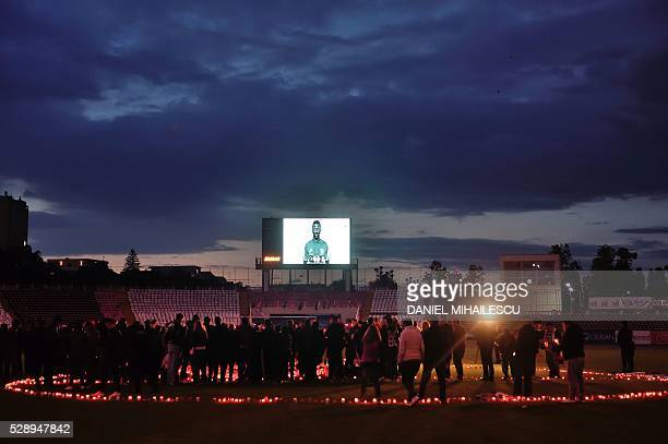 Fans of Dinamo Bucharest football team light candles and hold a vigil in memory of late Cameroonian international Patrick Ekeng in Bucharest on May 7...