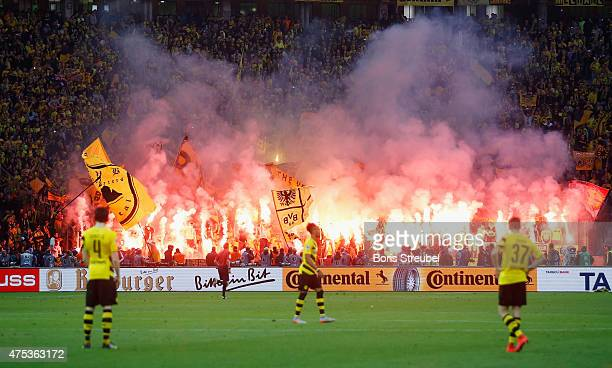 Fans of Dortmund burn flares during the DFB Cup Final match between Borussia Dortmund and VfL Wolfsburg at Olympiastadion on May 30 2015 in Berlin...