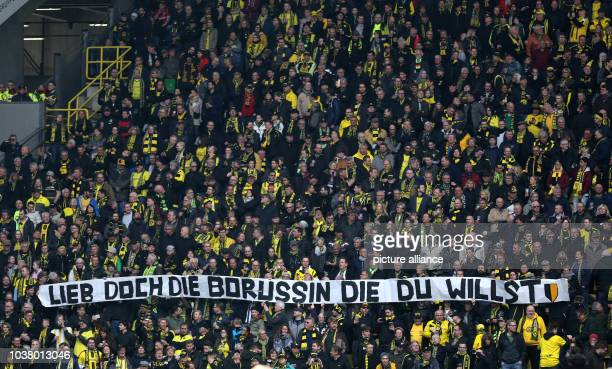 Fans of Dortmund hold up a banner against homophobia reading Lieb' doch die Borussin die du willst during the German Bundesliga soccer match between...