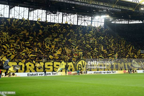 Fans of Dortmund wave flags during the Bundesliga match between Borussia Dortmund and FC Schalke 04 at Signal Iduna Park on November 25 2017 in...