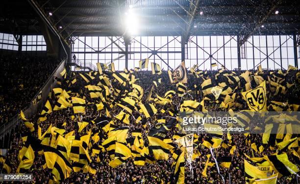 Fans of Dortmund wave their flags prior to the Bundesliga match between Borussia Dortmund and FC Schalke 04 at Signal Iduna Park on November 25 2017...