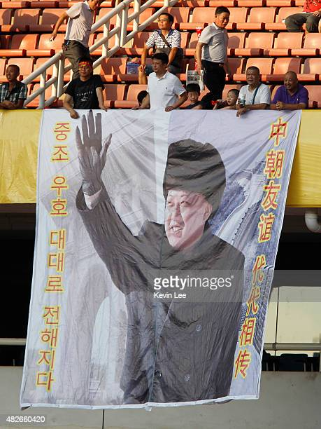 Fans of DPR Korea displays a portrait of Kim Jongun during the EAFF Women's East Asian Cup 2015 final round on August 1 2015 in Wuhan China