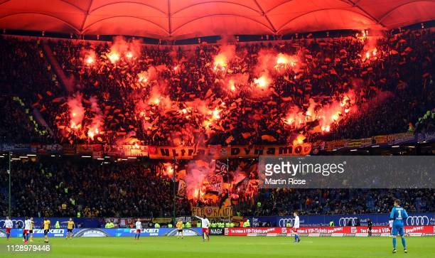 Fans of Dresden burn flares during the Second Bundesliga match between Hamburger SV and SG Dynamo Dresden at Volksparkstadion on February 11, 2019 in...