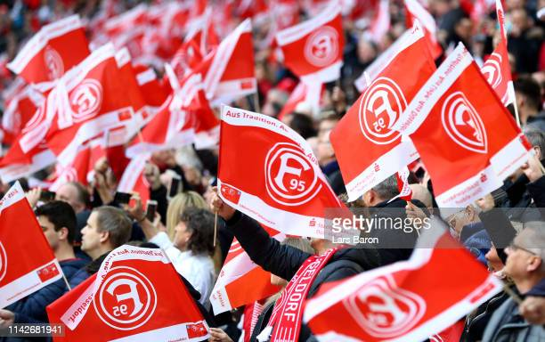 Fans of Duesseldorf wave flags during the Bundesliga match between Fortuna Duesseldorf and FC Bayern Muenchen at Esprit-Arena on April 14, 2019 in...