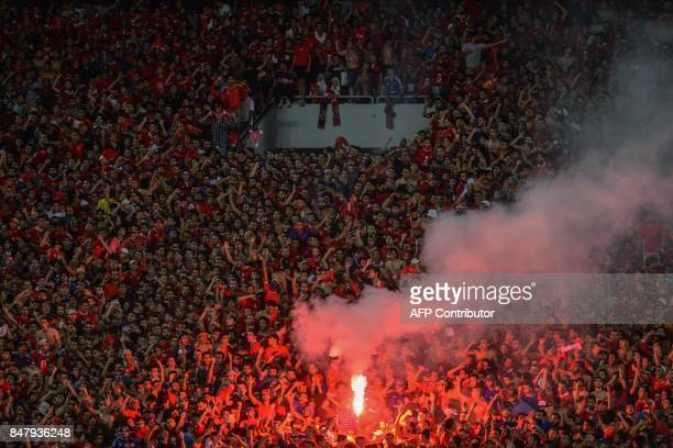 Fans of Egypt's AlAhly cheer for their team during the CAF Champions League quarterfinal firstleg football match between AlAhly and Esperance...