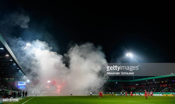 Fans of Eintracht Frankfurt burn flares / firework during the DFB Cup match between 1 FC Heidenheim and Eintracht Frankfurt at VoithArena on December...